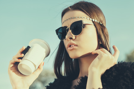 Hipster girl in sunglasses with cup of coffee. Close-up lifestyle outdoor toned portrait photo