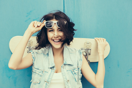 Young girl in sunglasses posing with skateboard  Lifestyle outdoor toned portrait