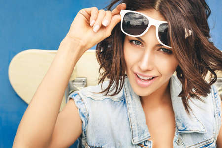 Close-up of girl in sunglasses posing with skateboard  Lifestyle outdoor portrait photo
