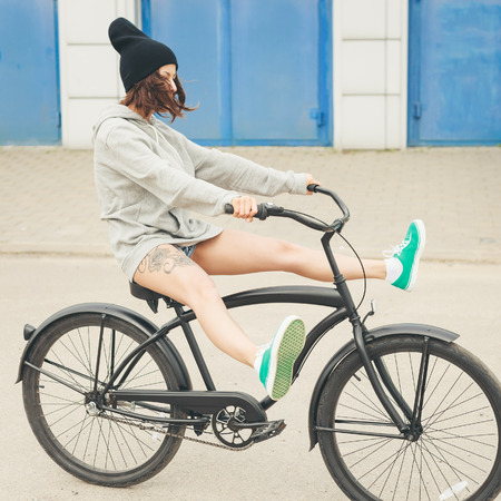 Young hipster girl riding black bike  Outdoor lifestyle portrait photo