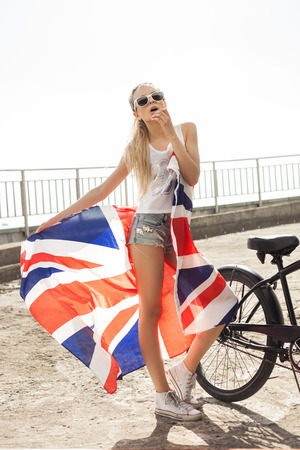 british girl: Pretty girl with flag and bike in sunrise time. Outdoor lifestyle portrait of sporty woman. Stock Photo