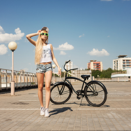 beach cruiser: Young woman standing next to beach bicycle. Outdoor lifestyle portrait of girl with cruiser.