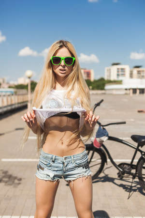Young woman standing next to black bicycle. Outdoor lifestyle portrait of swag girl. photo