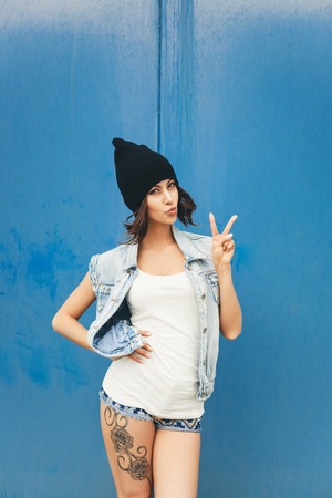 urban style: Cute hipster teenage girl with black beanie hat and tattoo Stock Photo