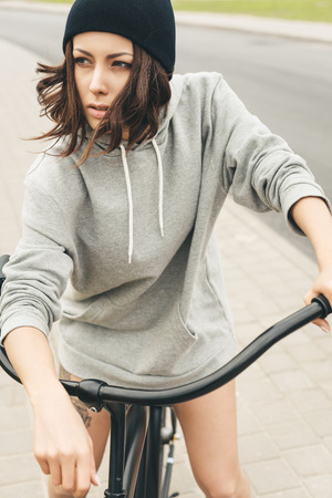 Young hipster girl with black bike. Outdoor lifestyle portrait Stock Photo