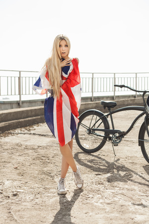 Girl wrap in flag with bike in sunrise time. Outdoor lifestyle portrait of young woman. photo