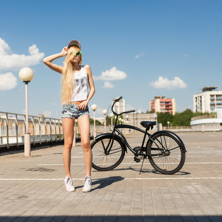 beach cruiser: Sexy woman standing next to beach bicycle. Outdoor lifestyle portrait of girl with black cruiser.