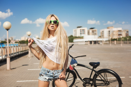 swag: Young woman standing next to black bicycle. Outdoor lifestyle portrait of cool girl. Stock Photo