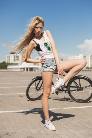 beach cruiser: Sexy young woman posing next to beach bicycle. Outdoor lifestyle portrait of girl with black cruiser.