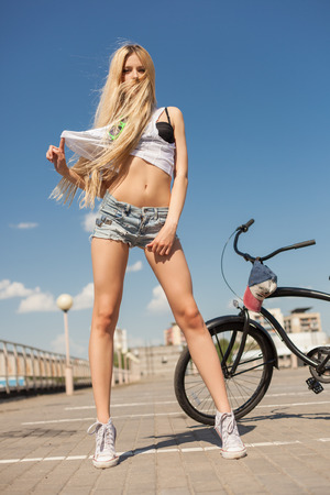beach cruiser: Sexy young blonde woman standing next to beach bicycle. Outdoor lifestyle portrait of girl with black cruiser. Stock Photo