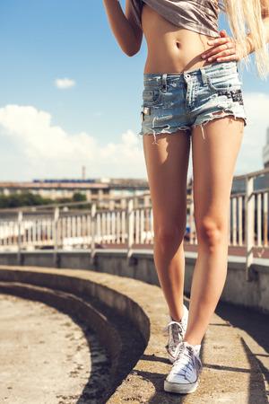 Jonge mooie blonde vrouw lopen op de straat in het wit gumshoes. buiten schot Stockfoto