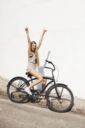 beach cruiser: Happy girl sitting on black beach bicycle. Outdoor lifestyle portrait of woman with cruiser. Stock Photo