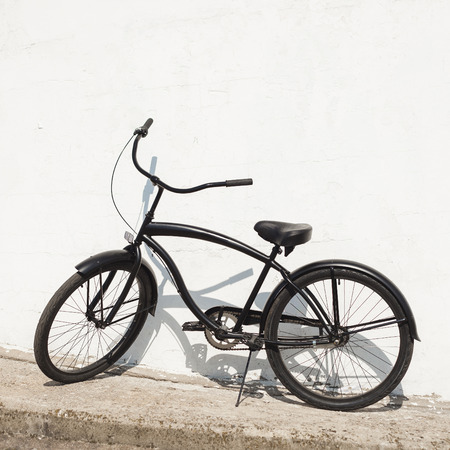 lesure: Black city bicycle cruiser standing by next white wall. Outdoor