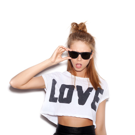 Sexy young woman with sunglasses looking at the camera.  White background, not isolated photo