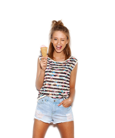 Pretty girl having fun and eating ice cream. Smeared face. White background, not isolated photo