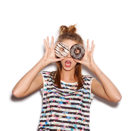 Playful girl holding donuts on her eyes. Woman showing own.  Stock Photo