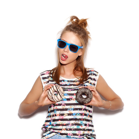 Young woman holding donuts on her bust. White background, not isolated