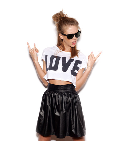 Young woman with sunglasses giving the Rock and Roll sign.  White background, not isolated photo