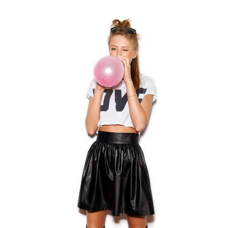 Young woman blowing a pink balloon .  版權商用圖片