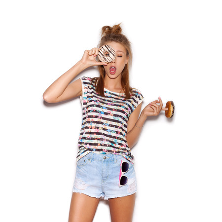 Playful girl holding donut on her eye.  White background, not isolated photo