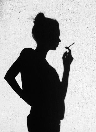 black girl smoking: Shadow of young woman with cigarette smoking around on wall background