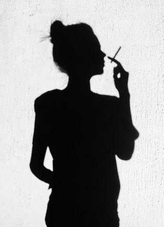 black girl smoking: Shadow of bad girl with cigarette smoking around on wall background