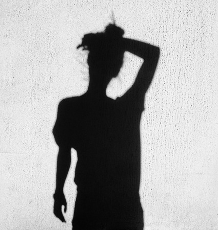 girl shadow: shadow of tired woman wiping forehead around on wall background Stock Photo