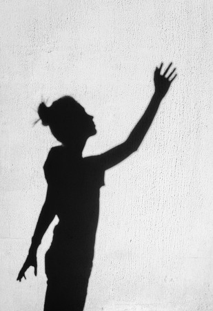 Girl stretching her hand toward the sky around on the wall background. Photo of shadows of woman
