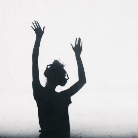 Woman with headphones lifting her hands up.  photo