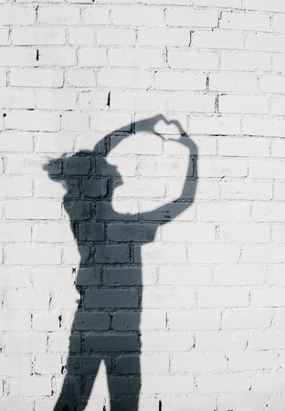 girl shadow: Portrait of a young woman showing a Heart with Her Hands around on the brick wall background. Stock Photo