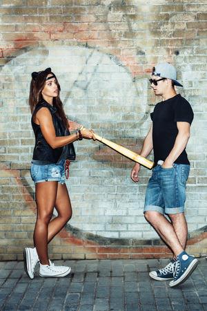 Bad girl with leather cat ears threatening baseball  bat guy. Urban scene. Outdoor lifestyle portrait photo