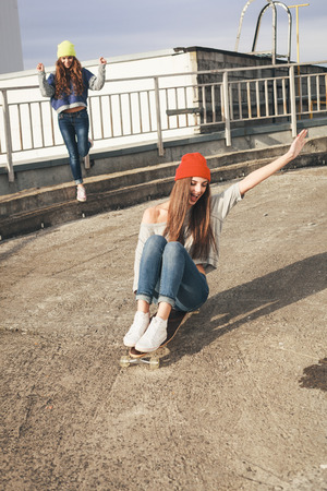 skate board: Two young  girl friends having fun. Downhill, longboarding . Outdoors, lifestyle.