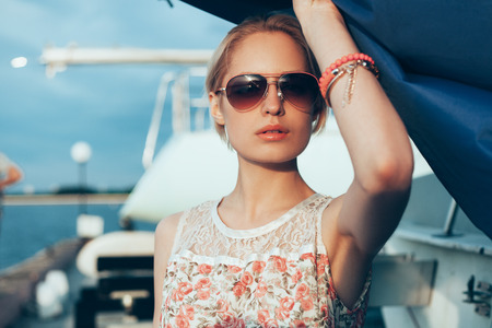 Blonde girl in flower dress and sunglasses holding  boat sails at sunset. Outdoor lifestyle portrait of woman photo