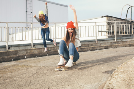Two young  girl friends having fun. Downhill, longboarding . Outdoors, lifestyle. photo