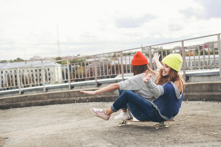 Two young  girl friends sitting together on longboard and having fun. Downhill, longboarding . Outdoors, lifestyle. photo
