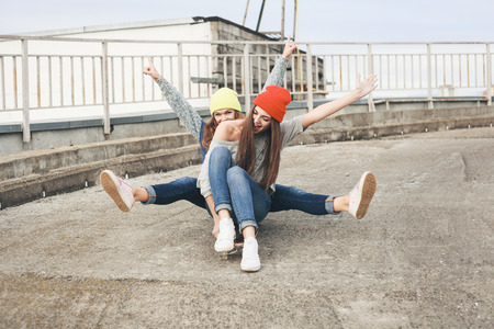 fun day: Two young  girl friends having fun. Downhill, longboarding . Outdoors, lifestyle.