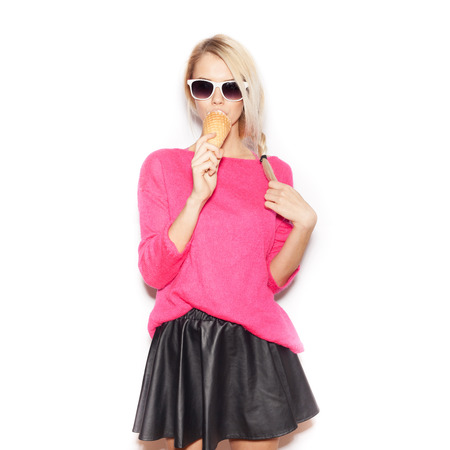 Pretty blonde girl eating ice cream. Indoor lifestyle portrait of woman in sunglasses.  White background, not isolated