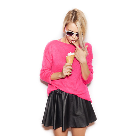 Pretty blonde girl eating ice cream. Indoor lifestyle portrait of woman in sunglasses.  White background, not isolated photo