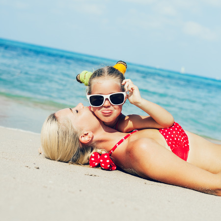 Young blonde mother and her little daughter having fun on the sea beach in summer. Outdoors photo