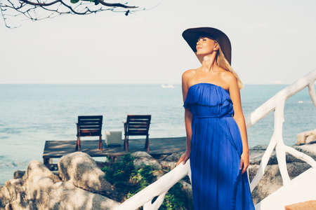 Young blonde woman wearing straw hat and elegant dress posing standing on beach. Outdoors photo