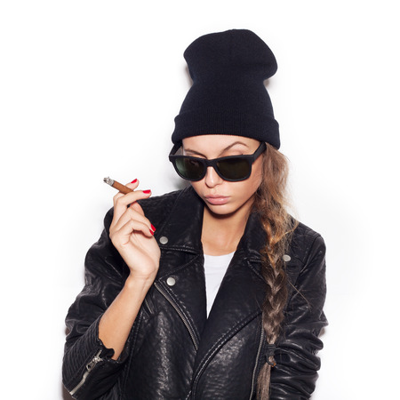 arrogant teen: Young woman in sunglasses and black leather jacket smoking cigar.  White background, not isolated Stock Photo