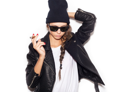 Hipster girl in sunglasses and black leather jacket smoking cigar.  White background, not isolated photo
