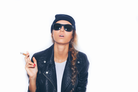 Naughty girl in sunglasses and black leather jacket smoking cigar.  White background, not isolated photo