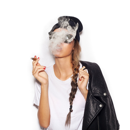 Young girl in sunglasses and black leather jacket smoking cigar.  White background, not isolated