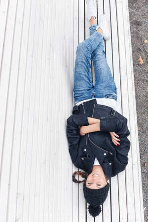 Beautiful young female lying on a park bench and lookin at camera. Outdoor lifestyle portrait of woman photo