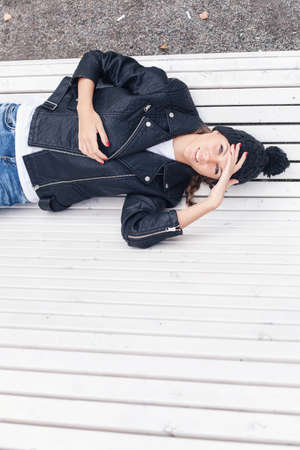 Beautiful young female lying on a park bench. Outdoor lifestyle portrait of woman photo