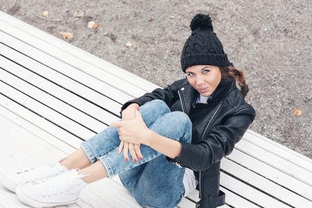 公園のベンチに座っているきれいな女の子。 写真素材