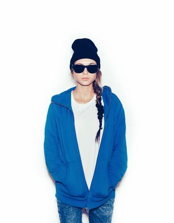 Hipster meisje in blauwe hoodie en zwarte muts tegen een witte achtergrond