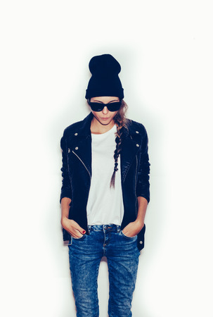 Girl  with sunglasses looking at floor.  White background, not isolated