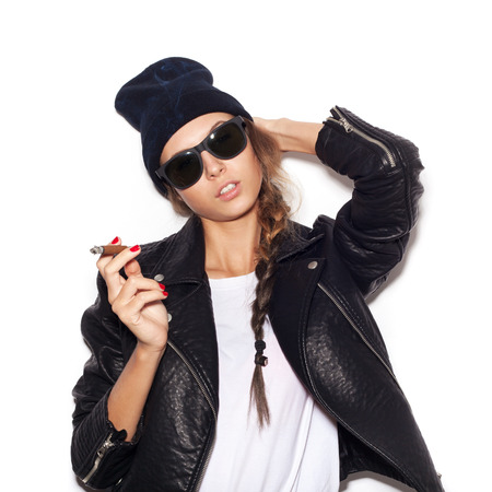 Young sexy woman in sunglasses and black leather jacket smoking cigar.   photo